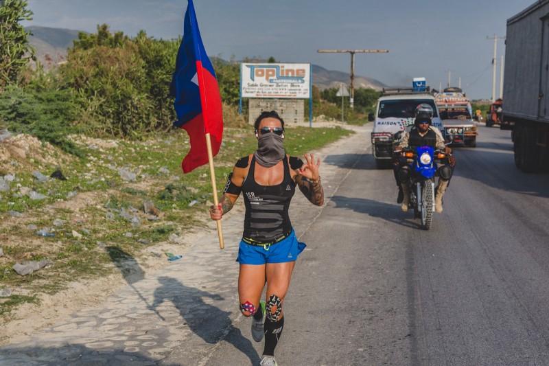 Ashley Horner runs for Haiti orphanage on Mightycause while holding flag.
