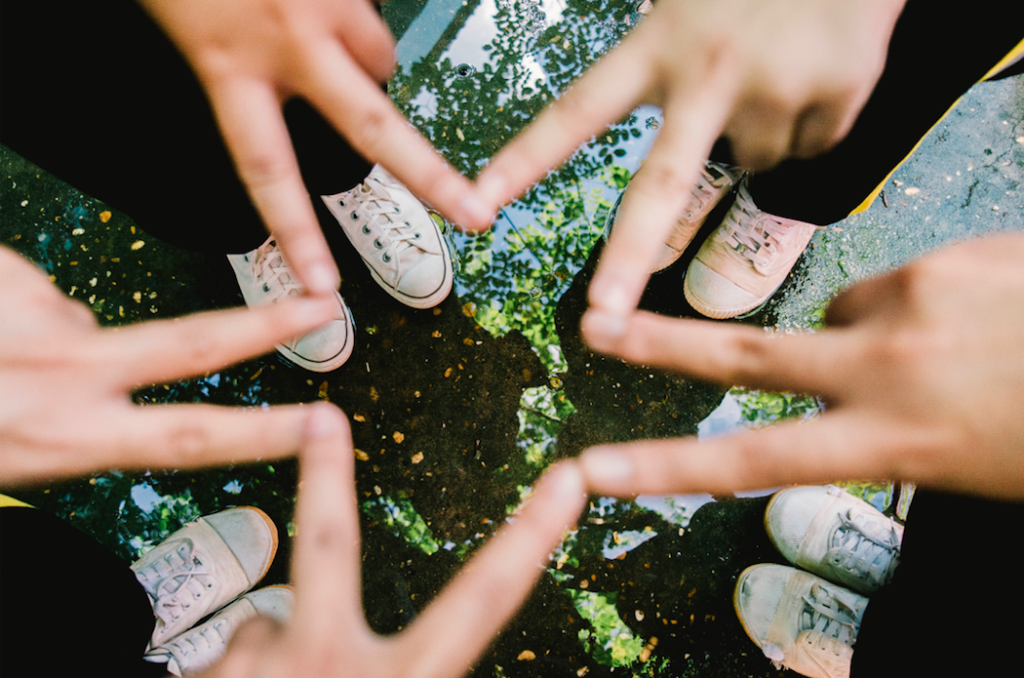 team of people standing in a circle making a star with their hands for fundraising