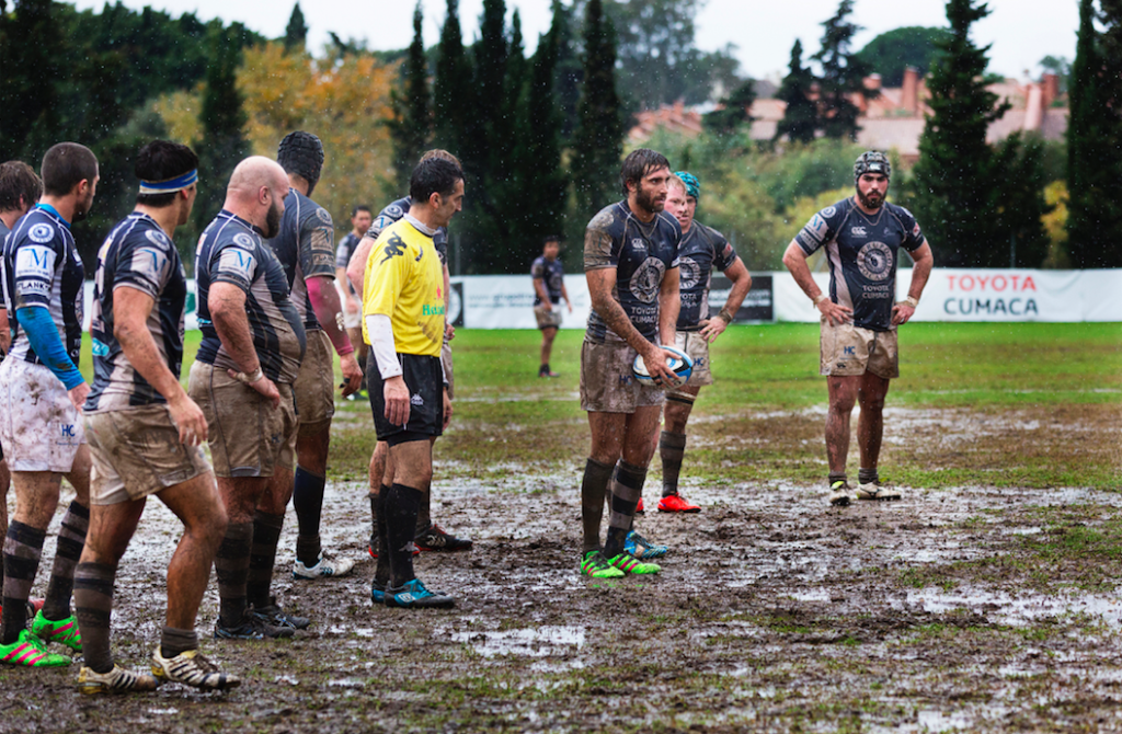 team of ruby player fundraisers playing on a muddy field