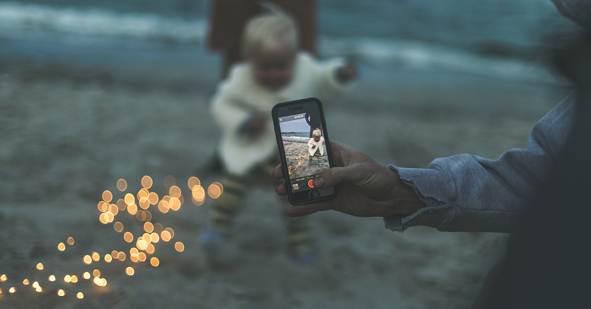 Person photographing small child with smartphone