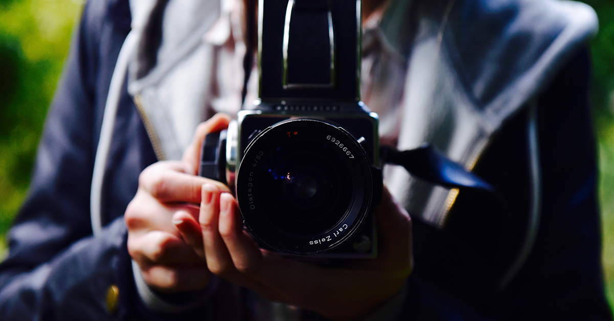 Close up photo of man holding a camera