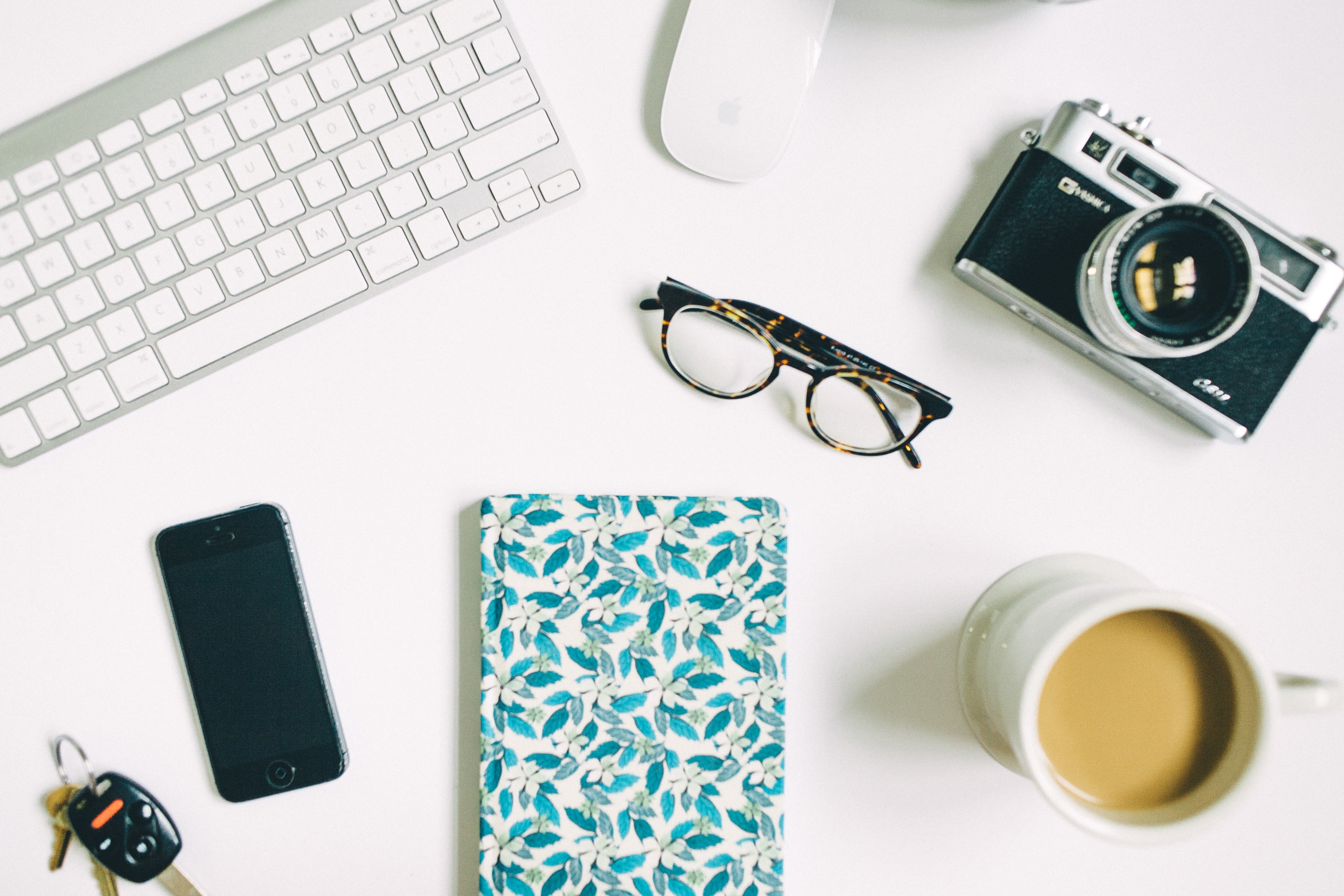 Image of computer, phone, notebook, glasses, camera & coffee