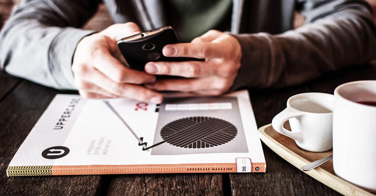 Person using mobile phone at table with a book