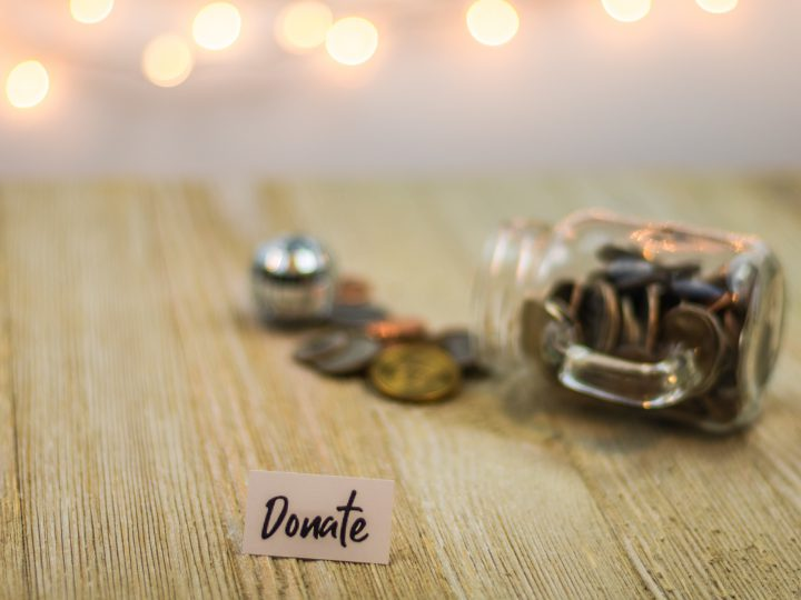 "image of coins spilling out of jar with sign that says ""donate"""