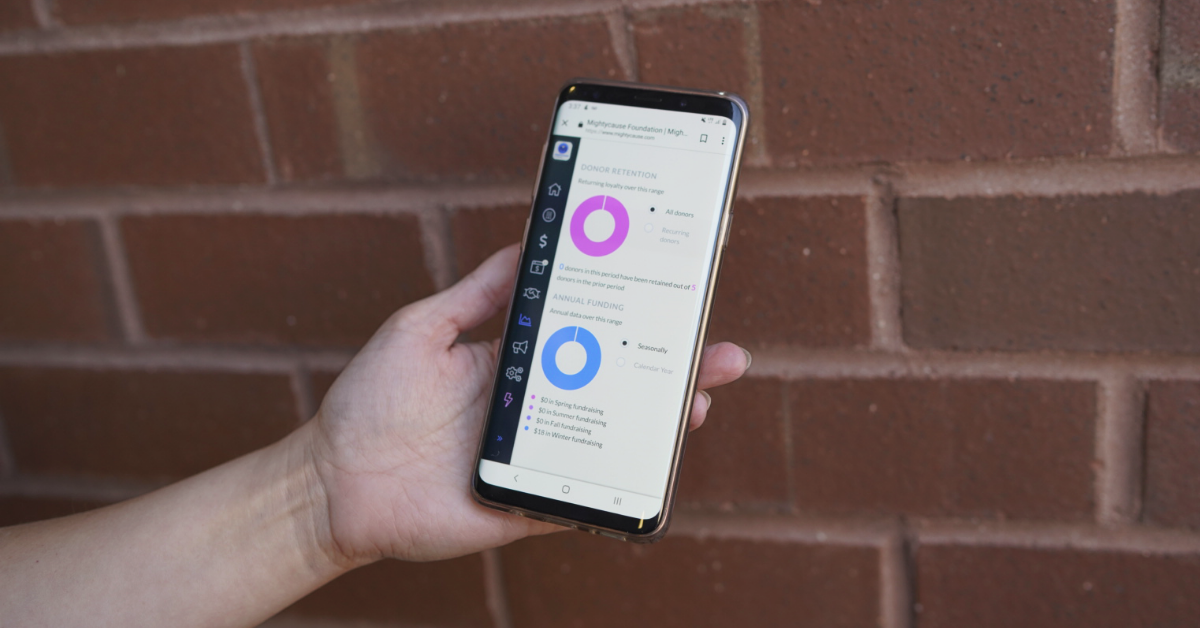 photo of mightycause advance analytics being viewed on a mobile phone in front of a brick wall