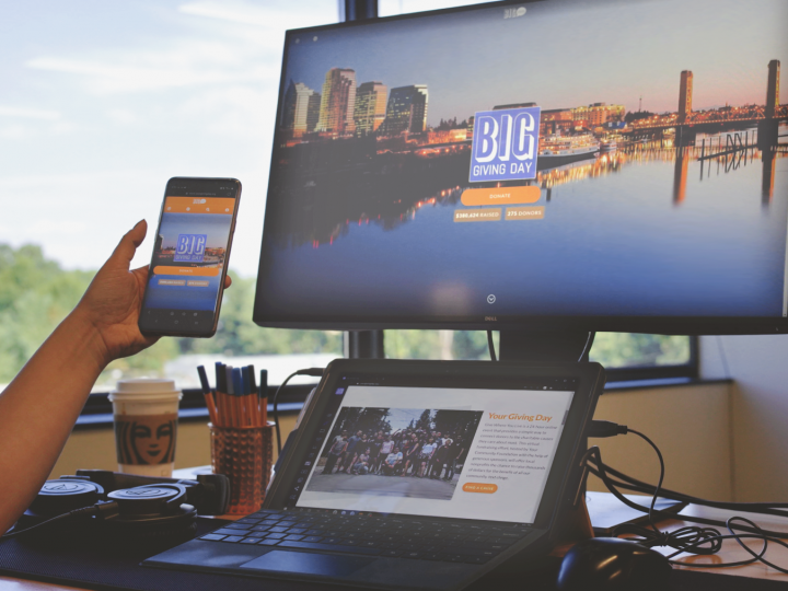 image of person holding phone with giving day site on it, in front of a desktop and tablet with the same website