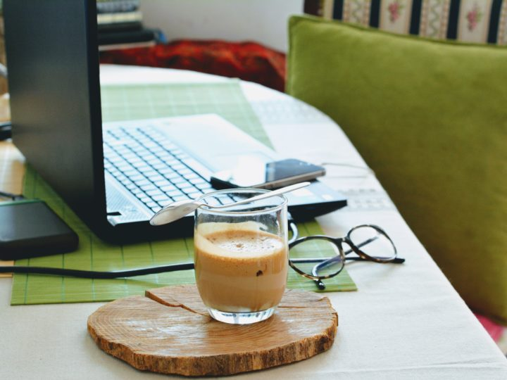 working remotely - image of laptop on a dining room table with coffee and glasses