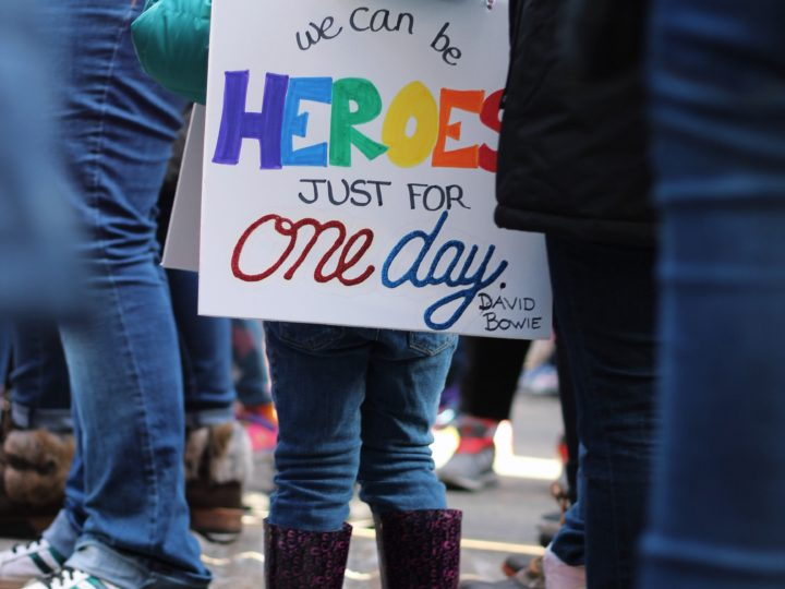 """what is a giving event: little girl wearing a sign that says """"we can be heroes just for one day"""""""