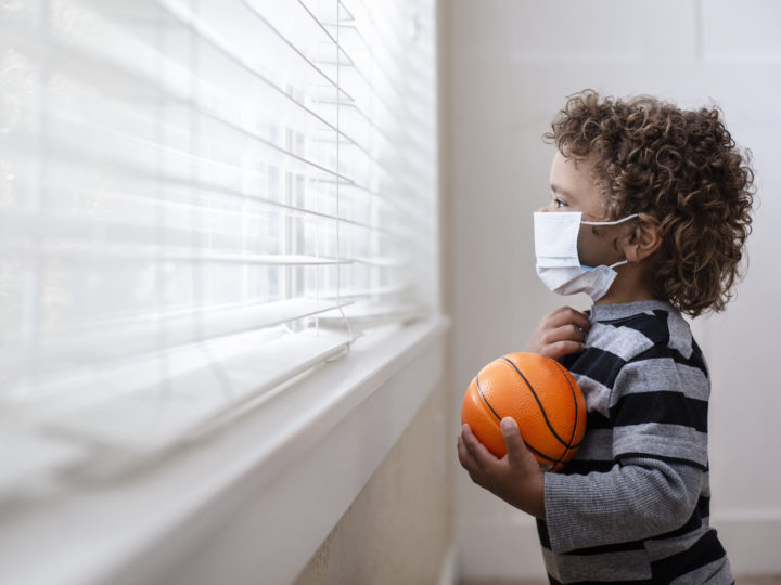summer fundraising: A young boy looking out the window holding his basketball wearing a protective facemark while seeking protection from COVID-19, or the novel coronavirus, by sheltering in place in his home.