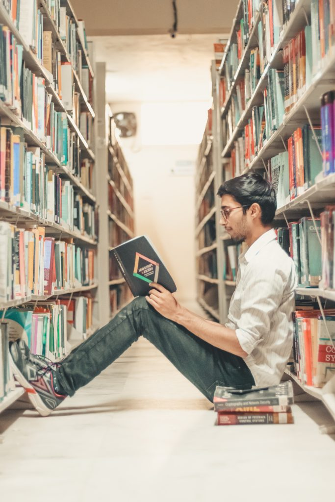 fundraising resources: man sitting in a library reading