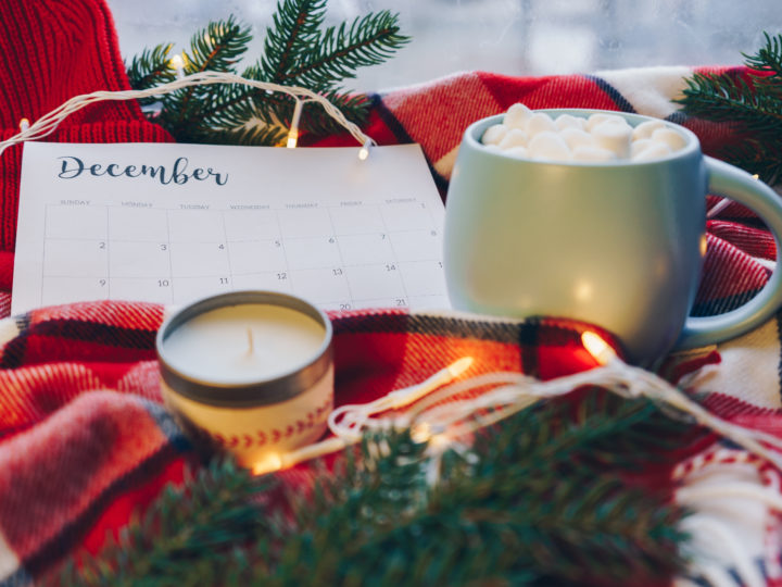 year-end emails: photo of hot cocoa cup, candle, christmas lights & December calendar on tartan fabric