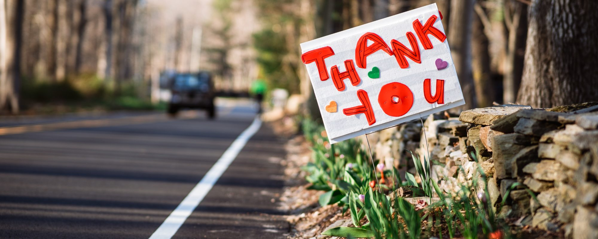 "how to thank donors: handmade sign on the sign of the road that reads ""thank you"""