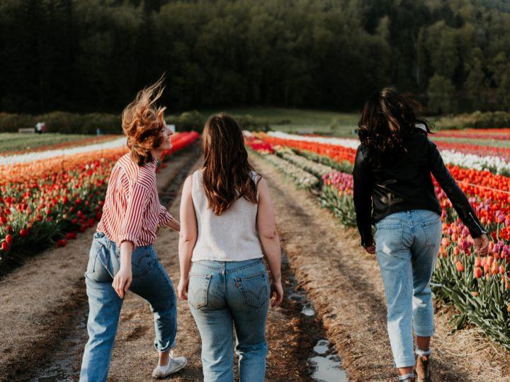 givingtuesday stewarding: 3 young girls running down a field