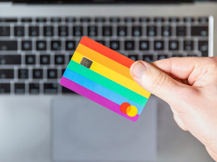 donation processor: person's hand holding a rainbow credit card over a laptop