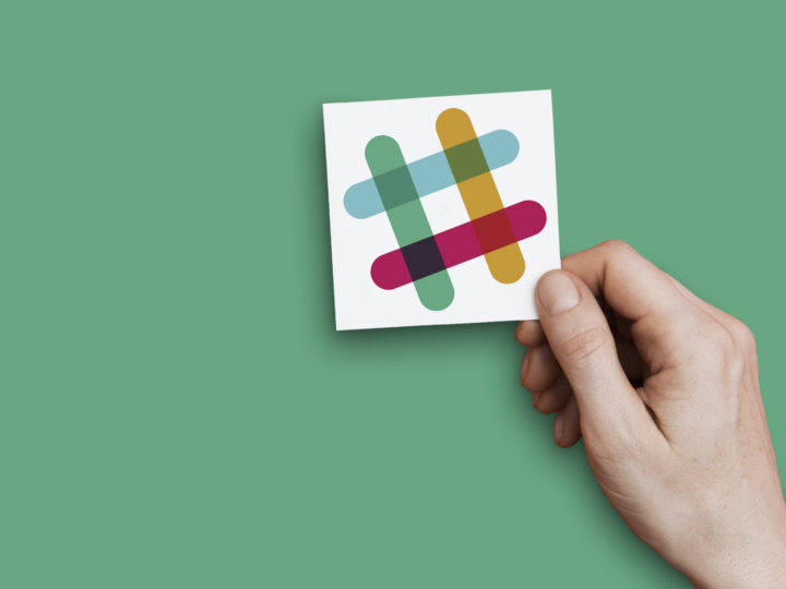 hand holding slack logo in front of a green background