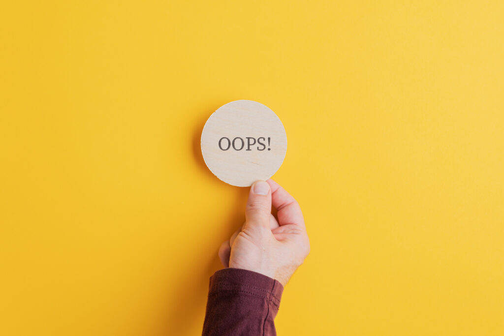 Male hand placing wooden cut circle with an Oops sign on it on bright yellow background.